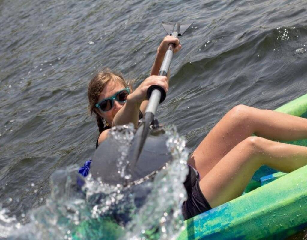Woman splashing the camera with her paddle and making a really cool photo